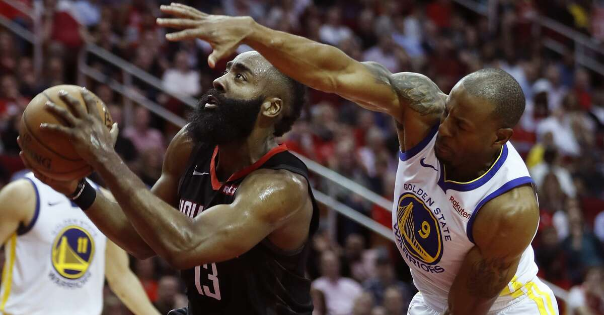 Houston Rockets guard James Harden (13) goes to the basket past Golden State Warriors guard Andre Iguodala (9) during the second quarter of an NBA basketball game at Toyota Center on Wednesday, March 13, 2019, in Houston.