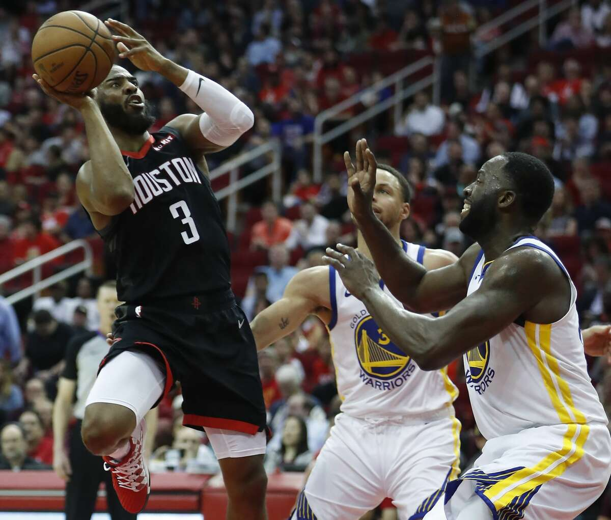 Houston Rockets guard Chris Paul (3) takes a shot against Golden State Warriors guard Stephen Curry (30) and forward Draymond Green (23) during the third quarter of an NBA basketball game at Toyota Center on Wednesday, March 13, 2019, in Houston.
