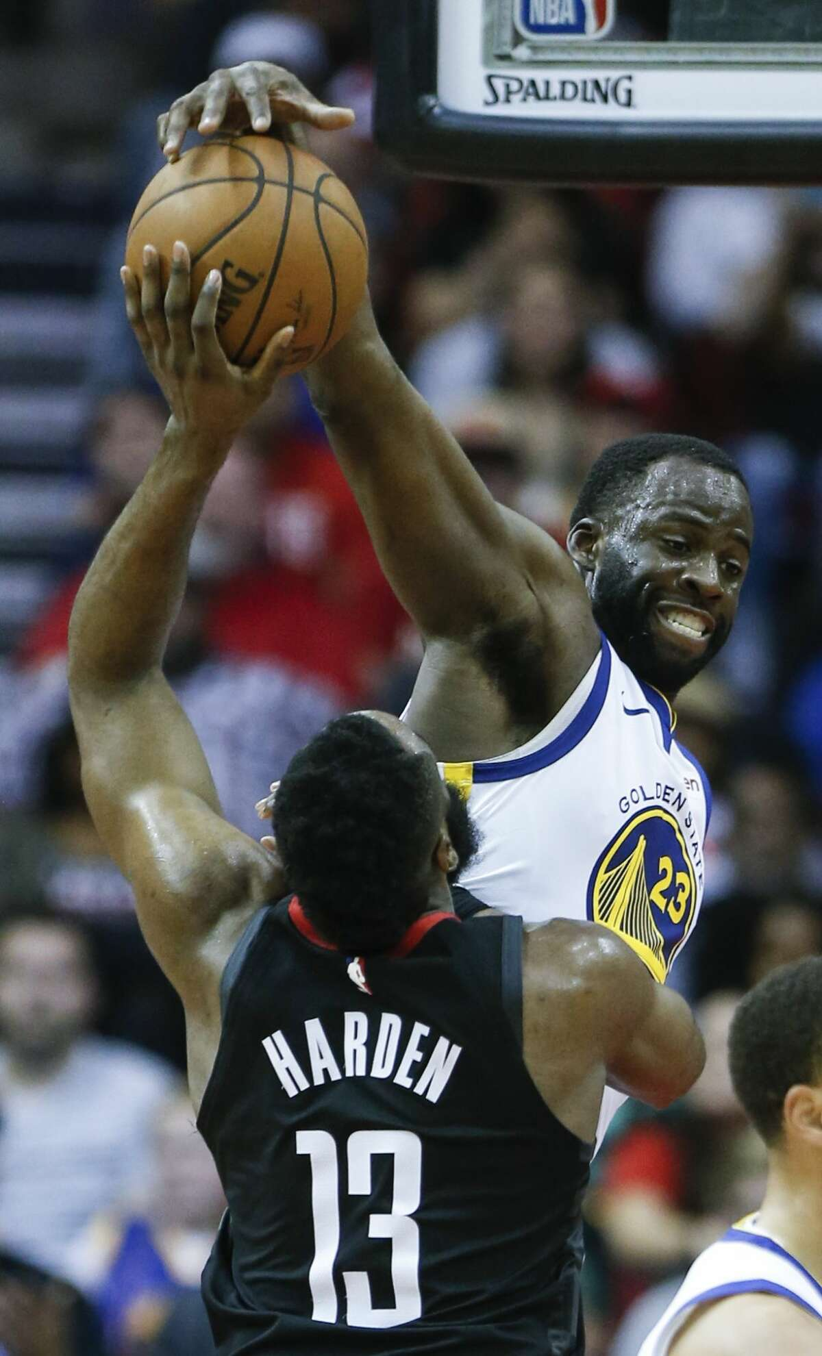 Golden State Warriors forward Draymond Green (23) blocks a shot by Houston Rockets guard James Harden (13) during the fourth quarter of an NBA basketball game at Toyota Center on Wednesday, March 13, 2019, in Houston.