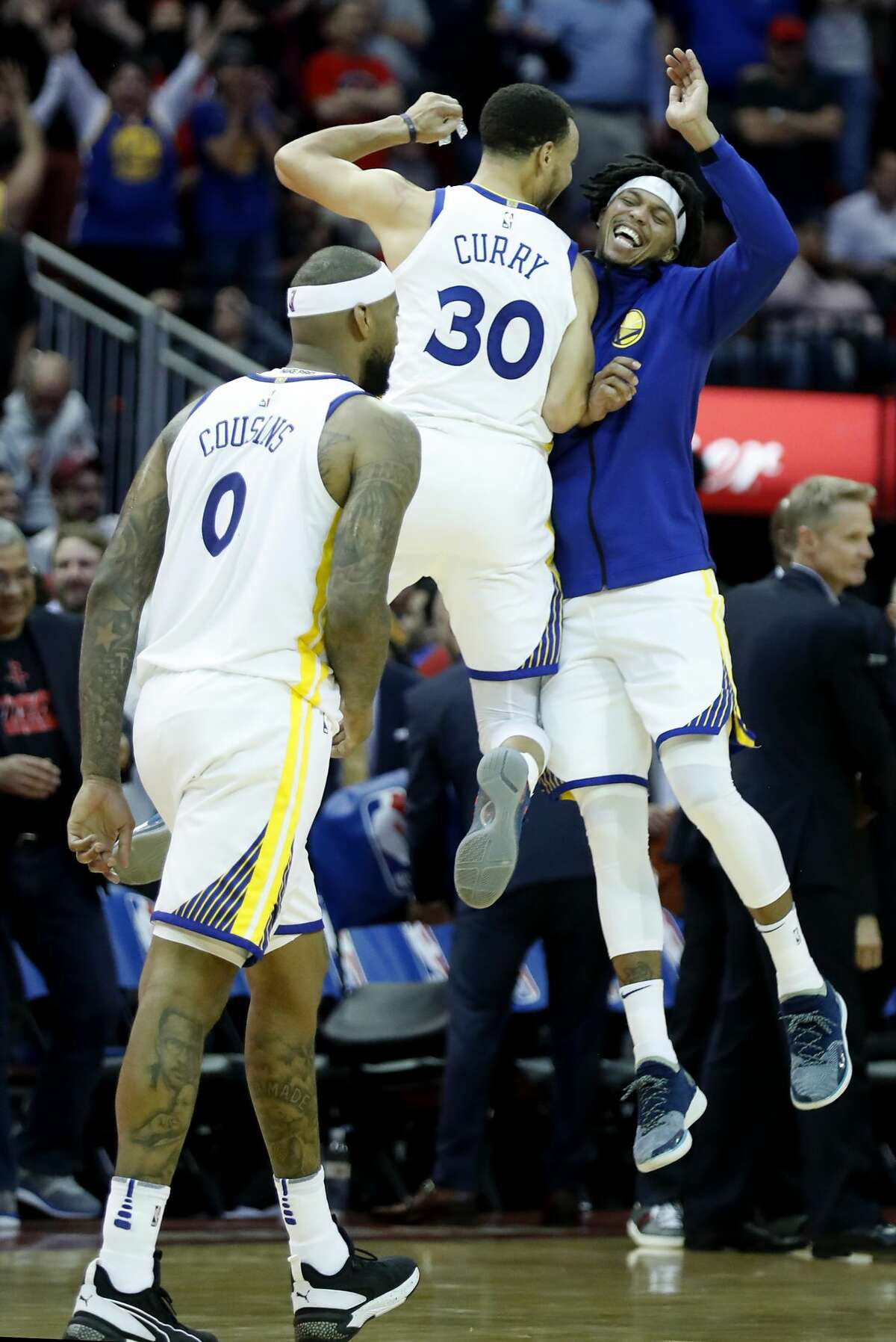 Golden State Warriors guard Stephen Curry (30) and Golden State Warriors guard Damion Lee celebrate the Warriors 106-104 win over the Houston Rockets in an NBA basketball game at Toyota Center on Wednesday, March 13, 2019, in Houston.