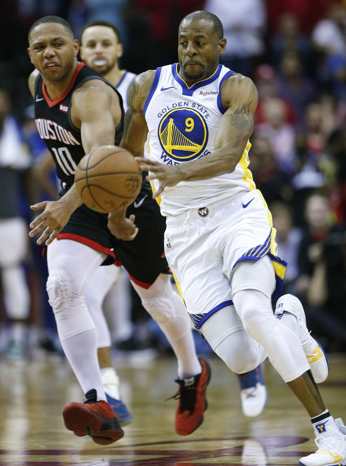 Golden State Warriors guard Andre Iguodala (9) and Houston Rockets guard Eric Gordon (10) chase after a loose ball knocked past half court after James Harden missed a free throw near the end of the fourth quarter of an NBA basketball game at Toyota Center on Wednesday, March 13, 2019, in Houston.