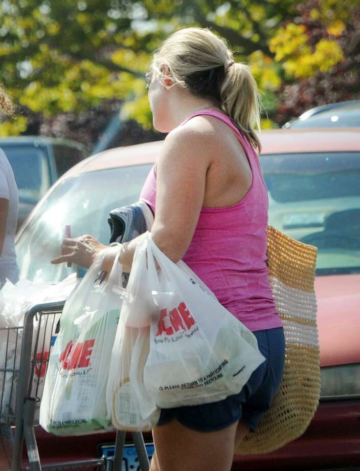 Before the ban: A customer carrying plastic shopping bags leaves the Riverside Commons Shopping Center in Greenwich, Conn., Tuesday, Sept. 4, 2018. A town ban on plastic bags goes into effect on Sept. 12. Photo: File. / Hearst Connecticut Media / Greenwich Time