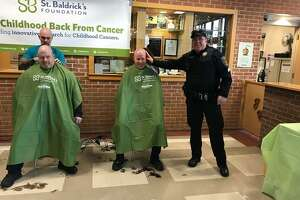 Redding police officers get their heads shaved during Joel Barlow High School's St. Baldrick's event on March 11, 2019.