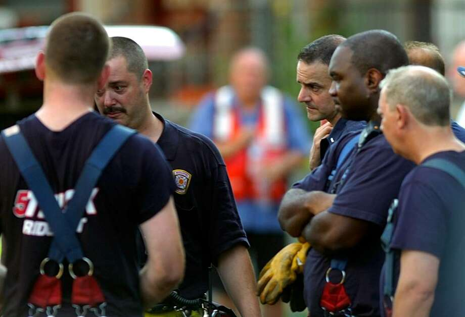 Firefighters stand outside the house at 41 Elmwood Ave. Saturday after a fire in the structure claimed the lives of Lt. Steven Velazquez and Firefighter Michel Baik and injured three others on July 24, 2010. Photo: Lindsay Niegelberg / Connecticut Post