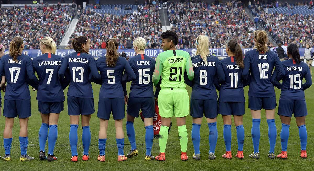 The United States women's national team stand arm-in-arm on the pitch wearing the names of women that inspire them on the back of their jerseys before playing England in a SheBelieves Cup women's soccer match Saturday, March 2, 2019, in Nashville, Tenn. (AP Photo/Mark Zaleski)