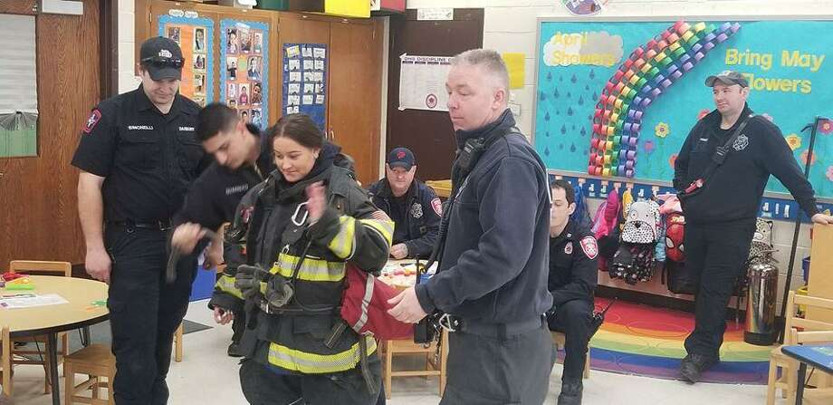 Danbury High School student Gabrielly Oliveira put on the firefighting gear during the firefighters' visit on March 14, 2019. Photo: Danbury Fire Department / Facebook