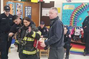 Danbury High School student Gabrielly Oliveira put on the firefighting gear during the firefighters' visit on March 14, 2019.