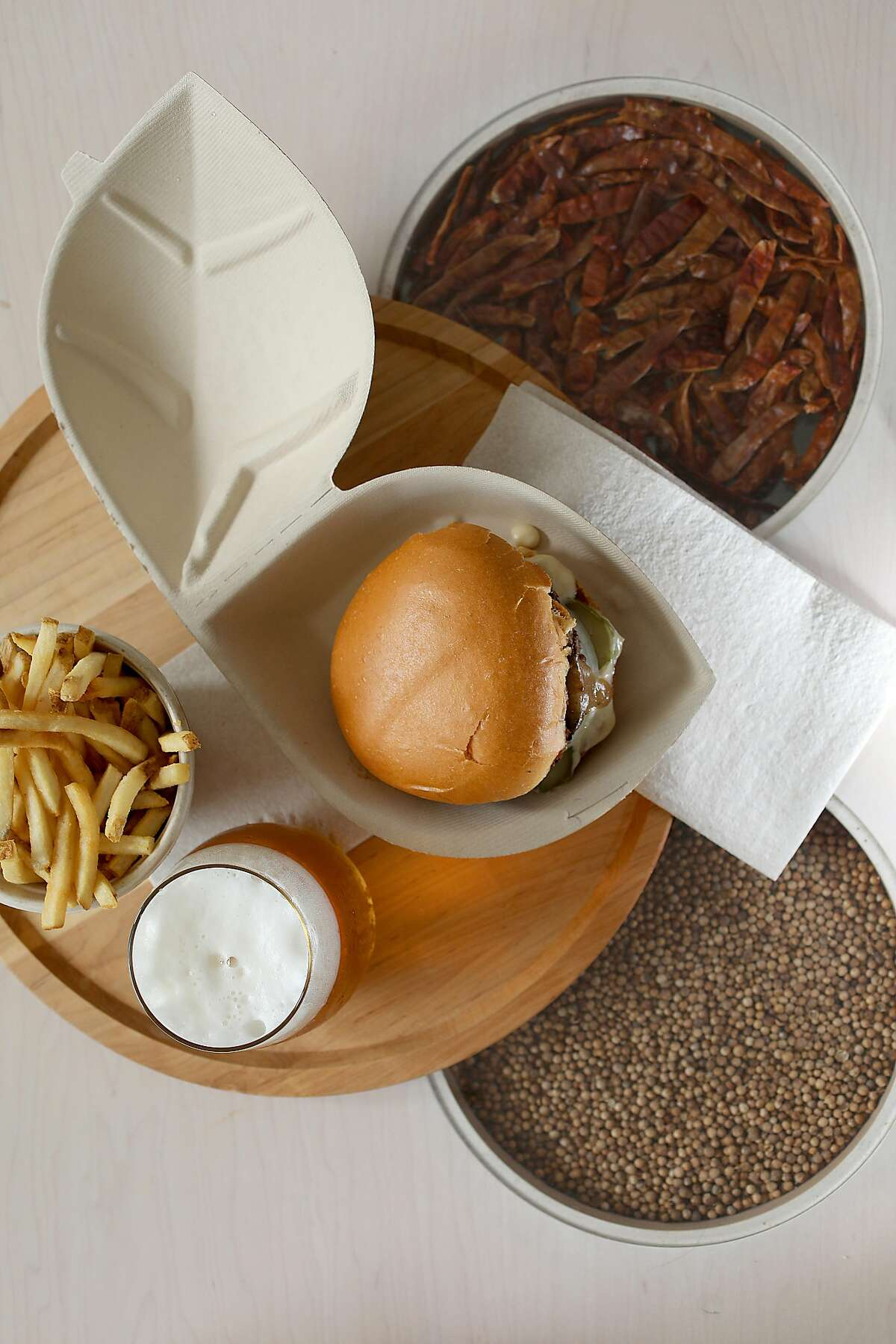 A Tumami Burger--creamy smoked oyster aioli, shiitake mushroom sauce, pickles, and onion--with fries and a beer on tap served at the Creator, the first robot-made burger restaurant seen on Wednesday, March 6, 2019, in San Francisco, Calif.