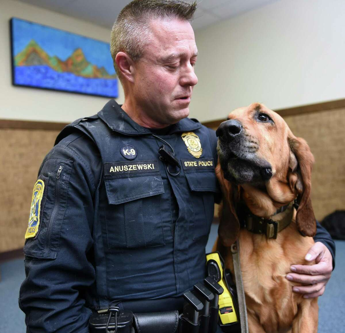 Trooper 1st Class Edward Anuszewski, of the state police, with his K-9 partner, Texas, a bloodhound tracking dog, at the State Police Canine Unit Training Center in Meriden on Monday.