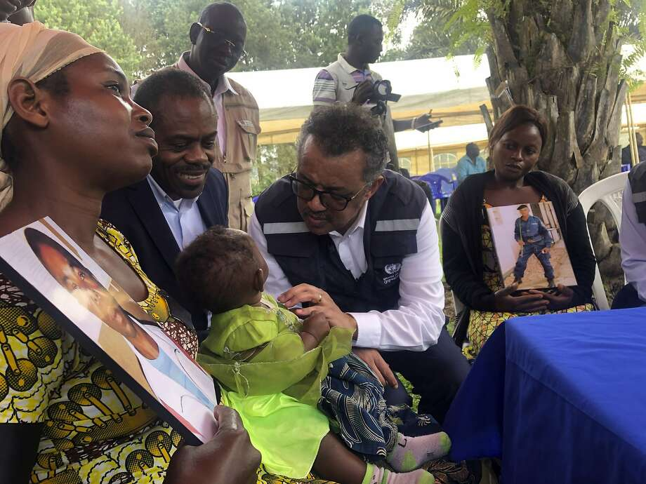WHO Director Tedros Adhanom Ghebreyesus (with glasses) meets with widows who lost their husbands at an Ebola treatment center in Butembo. Photo: Dalia Lourenco / Associated Press
