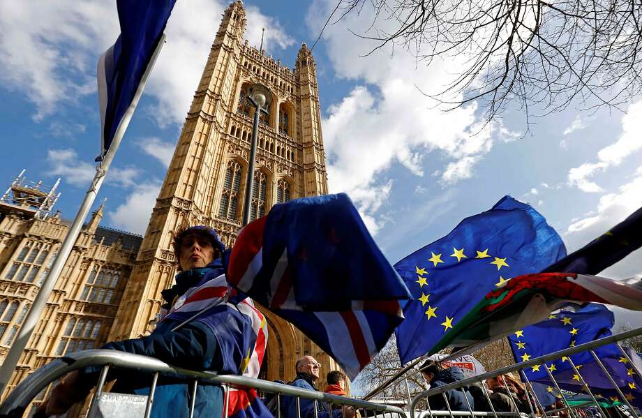 Pro-Brexit and anti-Brexit protesters hold flags as they demonstrate outside the Houses of Parliament as its members debate on whether to seek a delay to Britain's exit from the EU. Photo: Tolga Akmen / AFP / Getty Images