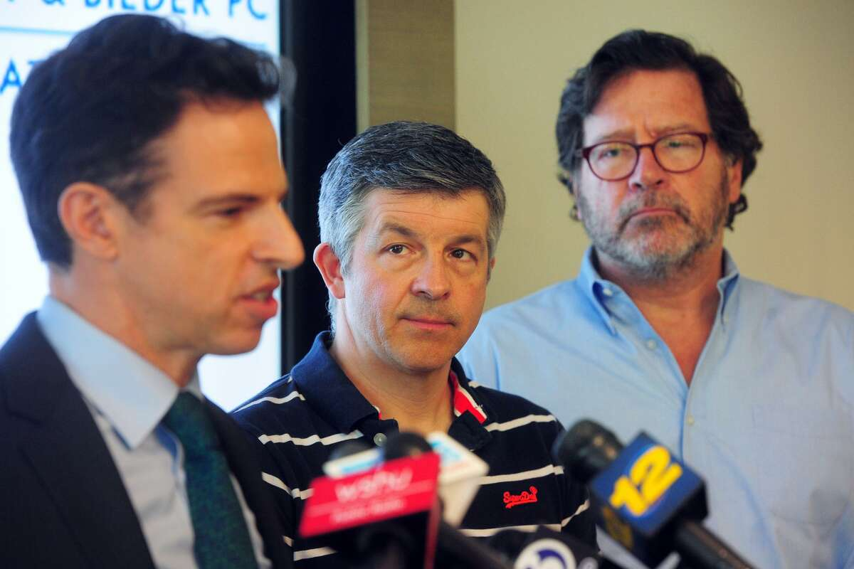 Ian Hockley, center, father of Sandy Hook Elementary School student Dylan Hockley, and Bill Sherlach, right, husband of Sandy Hook Elementary School psychologist Mary Sherlach, look on as attorney Josh Koskoff speaks a press conference in Bridgeport on Thursday.