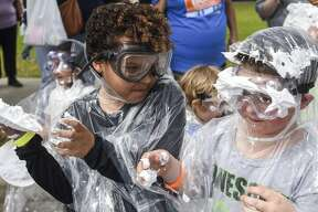 Sky Morgan, 9, on the left, throws a pie made out of shaving cream at another participant during a Pi Day pie fight. Over 80 shaving cream cans were used to make pies for around 100 children from 5 to 14 so they could have the shaving cream fight outside the Event Centre Thursday in celebration of Pi Day. This was Beaumont Children's Museum first time putting on the event and they plan on making this an annual event. Photo taken on Thursday, 03/14/19. Ryan Welch/The Enterprise