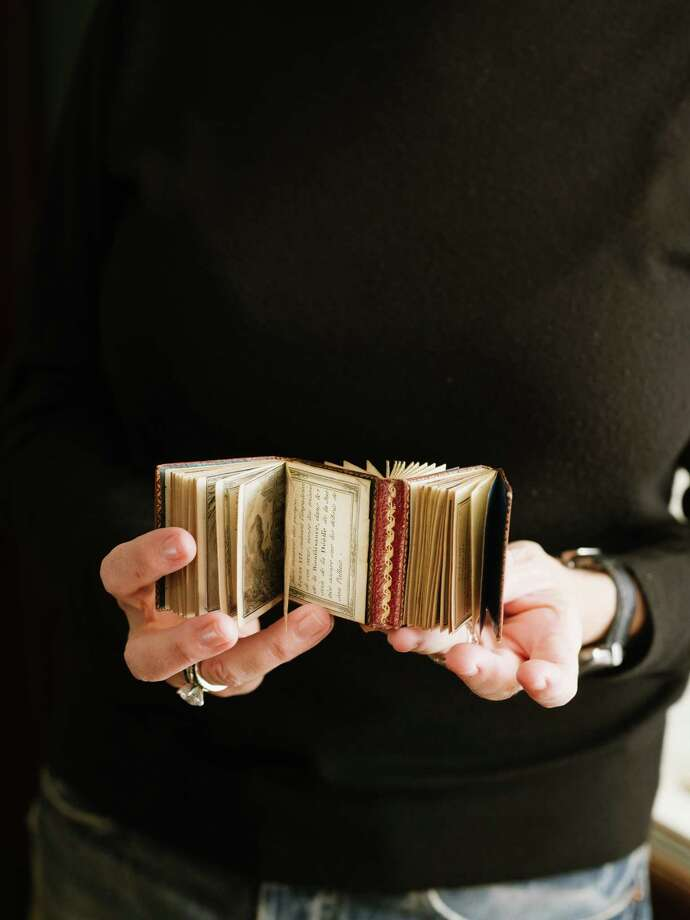 """Patricia Pistner holds one of the selections from """"A Matter of Size: Miniature Bindings and Texts from the Collection of Patricia J. Pistner,? at the Grolier Club in New York, March 1, 2019. About 950 books from Pistner?s authoritative collection, most about one to three inches high, are currently on display here. (Charlie Rubin/The New York Times) Photo: CHARLIE RUBIN / NYTNS"""
