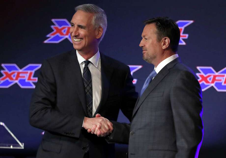 Oliver Luck, XFL Commissioner and CEO greets Bob Stoops after Luck introduced during a news conference as the new general manager and head coach of the Dallas XFL football team in Arlington, Texas, Thursday, Feb. 7, 2019. (AP Photo/Tony Gutierrez) Photo: Tony Gutierrez / Associated Press / Copyright 2019 The Associated Press. All rights reserved.