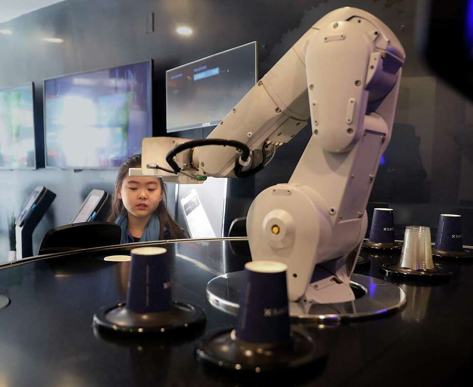 Olivia Jeon, 9 years old, from Toronto watches as robot picks a cup to make a cappuccino for her mother at Cafe X on Market St. on Friday, March 8, 2019, in San Francisco, Calif. Photo: Liz Hafalia,  Staff / The Chronicle / online_yes