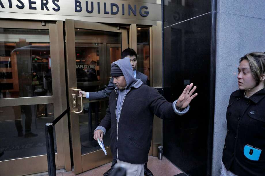 Hay Hov waves to supporters as he and his wife Catherine Depooter-Hov enter the U.S. Immigration and Customs Enforcement offices in San Francisco, Calif., where Hay will to turn himself over to ICE officials on Wednesday, March 13, 2019. Hov was told to turn himself in after being in the U.S. since he was 6 years old, brought by his parents, but he lost his green card at 19 when he was convicted of a crime. The Trump administration is now cracking down on Cambodians and other Southeast Asian undocumented immigrants. Photo: Carlos Avila Gonzalez / The Chronicle