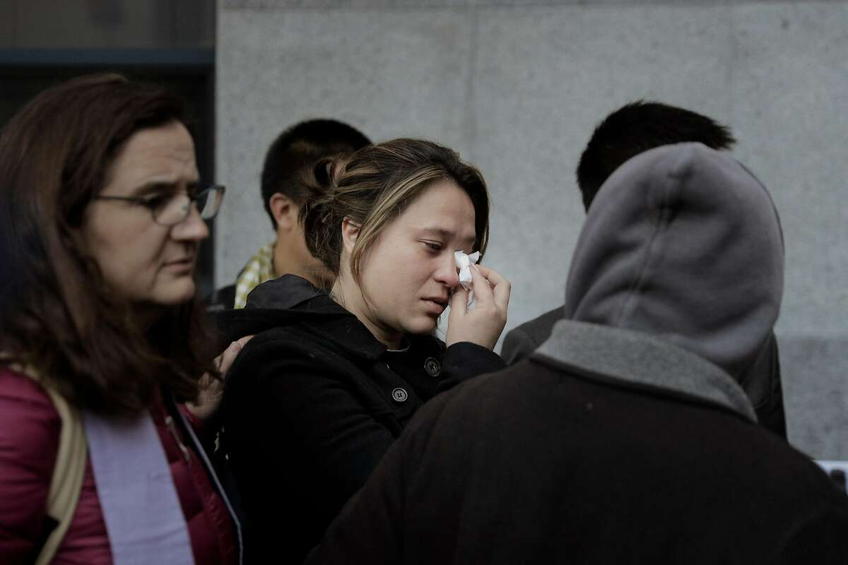 Catherine Depooter-Hov wipes away tears as she walks with her husband, Hay Hov, in front of the U.S. Immigration and Customs Enforcement building in San Francisco, Calif., where Hay will to turn himself over to ICE officials on Wednesday, March 13, 2019. . Hov was told to turn himself in after being in the U.S. since he was 6 years old, brought by his parents, but he lost his green card at 19 when he was convicted of a crime. The Trump administration is now cracking down on Cambodians and other Southeast Asian undocumented immigrants.