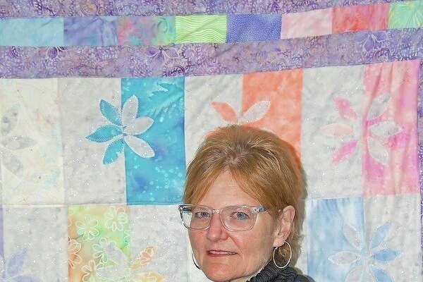 Dr. Laurey Hanselman stands beside a quilt she made, which hangs in her Pigeon office. (Bill Diller/For the Tribune)
