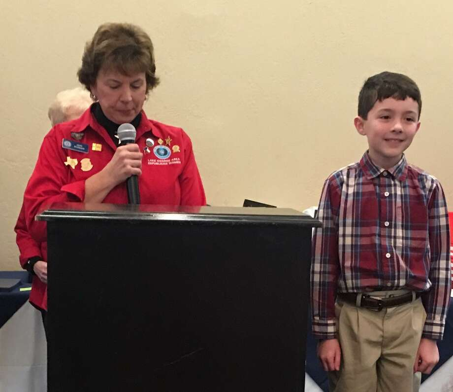 "Lake Conroe Area Republican Women met recently at April Sound Country Club for the 2019 ""My American Hero"" Awards Luncheon. Fifteen third graders from Willis ISD and 20 fifth graders from Montgomery ISD were honored at this event for their essays describing who was his or her ""American Hero"" and why. Shown here is LCARW member Janis Boulware presenting Adian Glasglow (from Mel Parmley Elementary School) an award for his essay on President George Herbert Walker Bush. Photo: Photo Courtesy The LCARW"