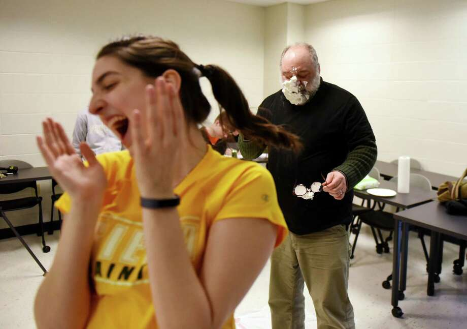 Brianna Murphy, Siena College math club president, left, is elated after after landing a foam pie on the school's Science Dean, John Cummings, during a Pi Day fundraiser for the Siena math club on Thursday, March 14, 2019, at Siena College in Loudonville, N.Y. (Will Waldron/Times Union) Photo: Will Waldron, Albany Times Union / 40046427A