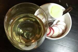 A glass of picpoul de pinet and an order of sliced radishes with butter from the new St. Mary's Strip wine bar Little Death