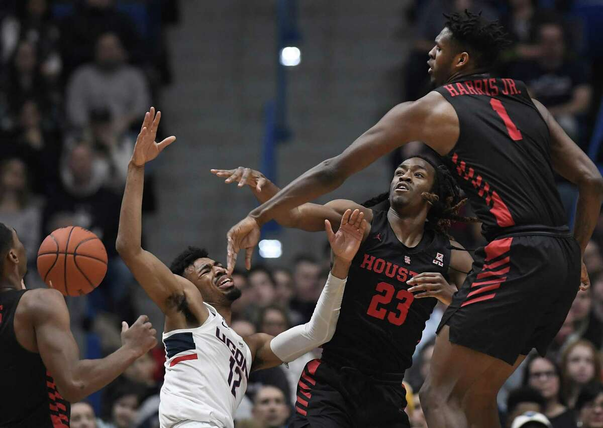 Houston's Chris Harris Jr. (1) blocks a shot attempt by Connecticut's Tyler Polley (12) as Houston's Cedrick Alley Jr. (23) defends during the second half of a game on Feb. 14 in Hartford.