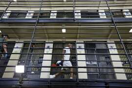 FILE - In this Aug. 16, 2016 file photo, a condemned inmate walks along the east block of death row at San Quentin State Prison in San Quentin, Calif. Gov. Gavin Newsom is expected to sign a moratorium on the death penalty in California Wednesday, March 13, 2019. (AP Photo/Eric Risberg, File)
