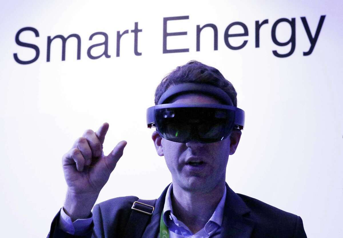 Amid moody and colorful lighting, conference attendant Guillaume de Cumond with Total, tries on an ABB augmented reality headset in the Microsoft room displaying various energy technologies during the second day of CERAWeek by IHS Markit at the George R. Brown Convention Center Tuesday, Mar. 12, 2019 in Houston, TX. CONTINUE to see scenes and high-profile speakers from CERAWeek 2019.