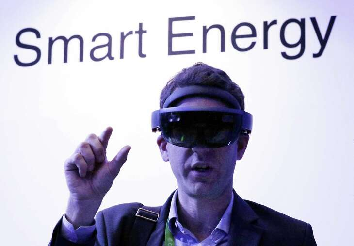 Guillaume de Cumond with Total tries on Microsoft's augmented reality headset at CERAWeek by IHS Markit in the Microsoft room displaying various energy technologies.