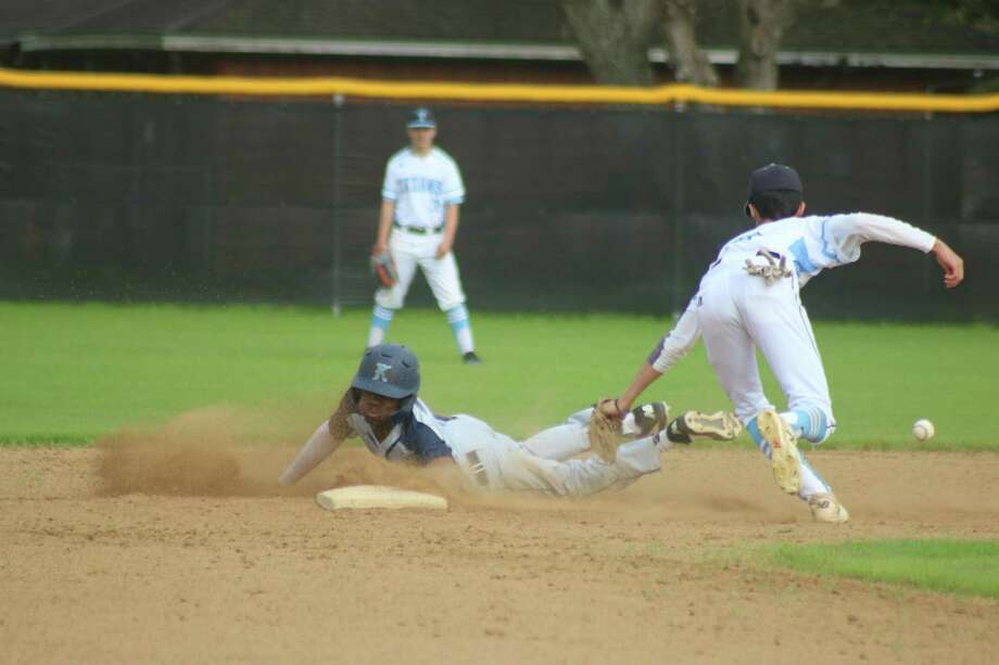 Tre Richardson swipes one of the four bases he stole during Thursday afternoon's 22-6A game at Pasadena's Maguire Field. He scored twice to help Kingwood up their district mark to 3-0. Photo: Robert Avery