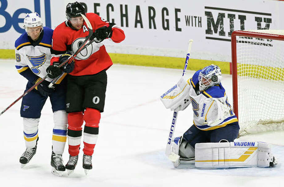 The puck passes the helmet of Blues goaltender Jake Allen (34) as defenseman Jay Bouwmeester (19) and Ottawa Senators right wing Bobby Ryan (9) skate in front of the crease during Thursday night's game in Ottawa. Photo: AP Photo