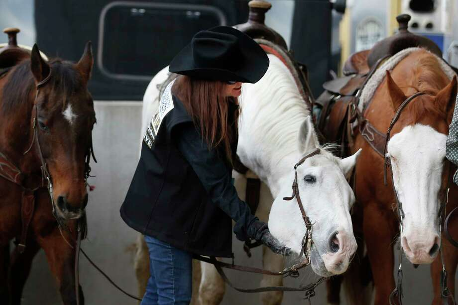 Debra Tibbetts, of Deer Park, scratches under the chin of John, a horse lined up to ride in the grand entrance during Rodeo Houston at NRG Stadium on Thursday, March 14, 2019, in Houston. Photo: Brett Coomer, Staff Photographer / © 2019 Houston Chronicle