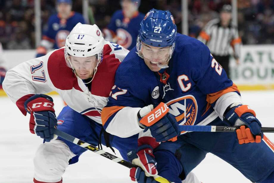 Montreal Canadiens defenseman Brett Kulak (17) and New York Islanders left wing Anders Lee (27) chase the puck during the second period of an NHL hockey game, Thursday, March 14, 2019, in Uniondale, N.Y. (AP Photo/Mary Altaffer) Photo: Mary Altaffer / Copyright 2019 The Associated Press. All rights reserved.