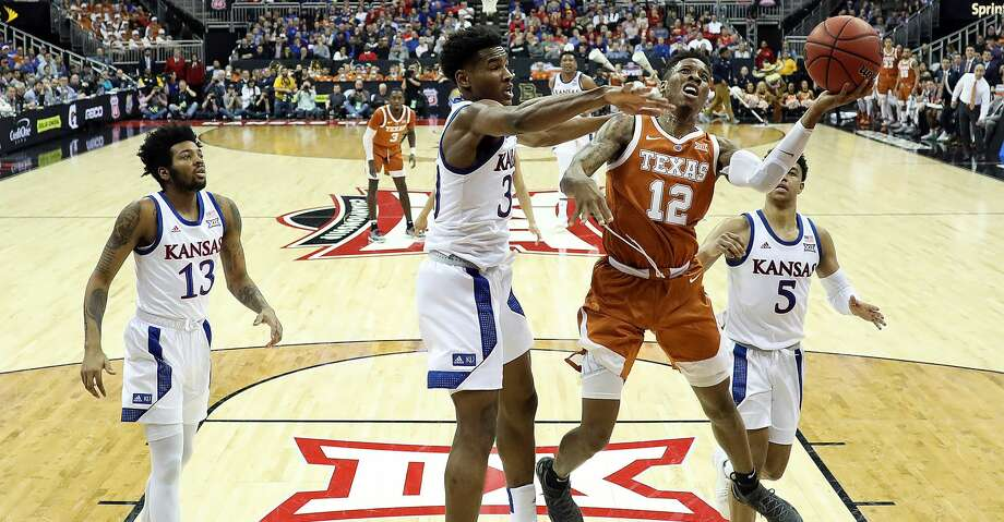 KANSAS CITY, MISSOURI - MARCH 14:  Kerwin Roach II #12 of the Texas Longhorns drives to the basket as Ochai Agbaji #30 of the Kansas Jayhawks defends during the quarterfinal game of the Big 12 Basketball Tournament at Sprint Center on March 14, 2019 in Kansas City, Missouri. (Photo by Jamie Squire/Getty Images) Photo: Jamie Squire/Getty Images