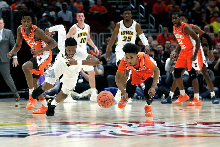 Isaiah Moss of Iowa (4) and Trent Frazier of Illinois chase a loose ball during Thursday night's second-round game at the Big Ten Conference tournament in Chicago. Photo: AP Photo