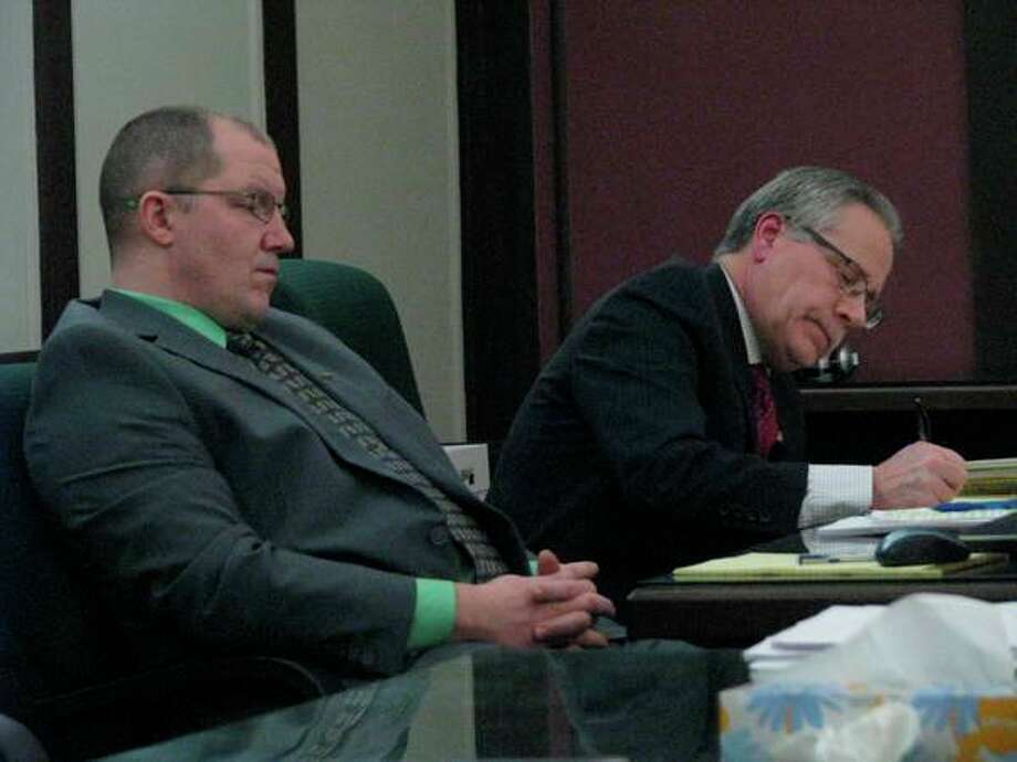 Officer Jeremy Davis of the Midland Police Department, left, and Midland County Prosecuting Attorney J. Dee Brooks listen to defense attorney Dan Duke's closing argument during the trial of Joel Brandon Wallace on March 14, 2019 in the 42nd Circuit Court.
