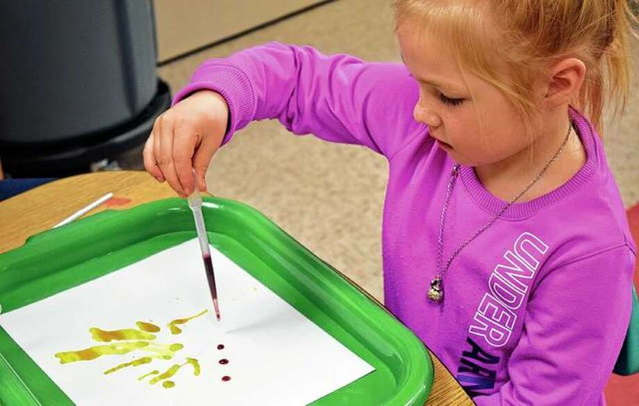 Avery Dyson, 5, makes a picture using drops of colored liquid and a straw Thursday at the Early Years Program. Photo: Samantha McDaniel-Ogletree | Journal-Courier