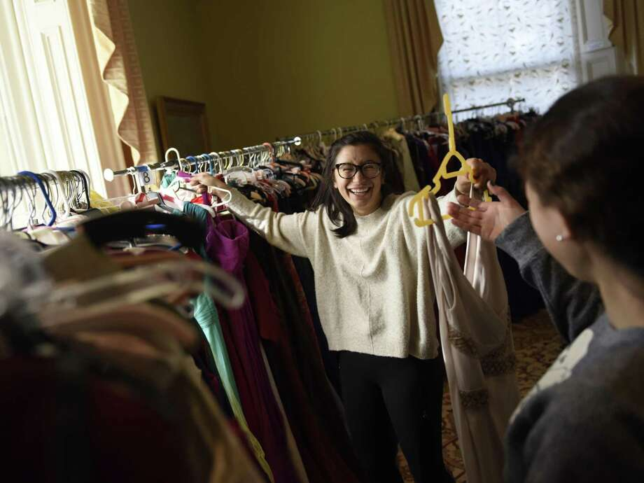 "Volunteer Zoe Metalios organizes prom dresses at the Greenwich United Way's Neighbor to Neighbor Prom Project Giveaway at the Tomes-Higgins House in Greenwich, Conn. Thursday, March 14, 2019. Donated prom dresses, tuxedos, shoes and accessories are available for free to Fairfield County and Westchester County students. ""Shopping"" continues Friday and Saturday at the Tomes-Higgins House. Photo: Tyler Sizemore / Hearst Connecticut Media / Greenwich Time"