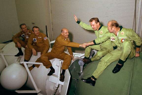 "The astronauts and cosmonauts sit atop mock-ups at NASA's Johnson Space Center in Houston. At left, the three Americans (left to right, Donald ""Deke"" Slayton, Vance Brand and Thomas Stafford) are seated on a mock-up of the docking module designed to link the Apollo and Soyuz spacecraft. The two Soviets (Valeriy N. Kubasov, left, and Aleksey A. Leonov) are atop a mock-up of a Soyuz spacecraft orbital module."