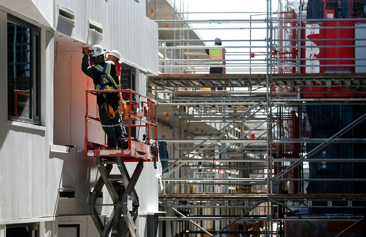 Construction work continues between buildings of The Landing apartment complex in the Dogpatch neighborhood of San Francisco, Calif. on Wednesday, March 13, 2019. Up to 20 percent of the tenants in the 263-unit complex will be allowed to rent their apartments or rooms through Airbnb.