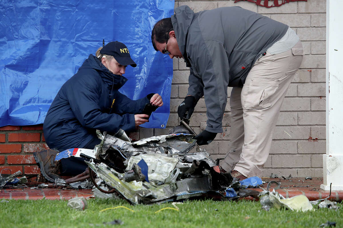 Maja Smith, left, National Transportation Safety Board investigator, and Ricardo Asensio, Senior Air Safety Investigator with Air Safety Investigations, investigates pieces of a Cessna airplane in front of a Yorba Linda, Calif., home after a plane crashed on February 4, 2019, killing the pilot and four people inside a home. (Allen J. Schaben/Los Angeles Times/TNS)