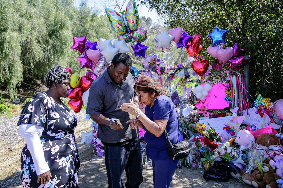 Anthony Jones, center, shares some memories of daughter Trinity Jones on his phone with Mary Montes at the make-shift memorial in Hacienda Heights. Grand mother Barbara Jones is seen on left. Trinity Jones body was found in a suitcase in Hacienda Heights, Calif. (Irfan Khan/Los Angeles Times/TNS) Photo: Irfan Khan/TNS