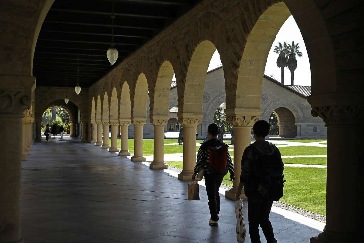 People walk on the Stanford University campus Thursday, March 14, 2019, in Stanford, Calif. In the first lawsuit to come out of the college bribery scandal, several students are suing Yale, Georgetown, Stanford and other schools involved in the case, saying they and others were denied a fair shot at admission. The plaintiffs brought the class-action complaint Wednesday, March 13, 2019, in federal court in San Francisco on behalf of themselves and other applicants and asked for unspecified damages. (AP Photo/Ben Margot)