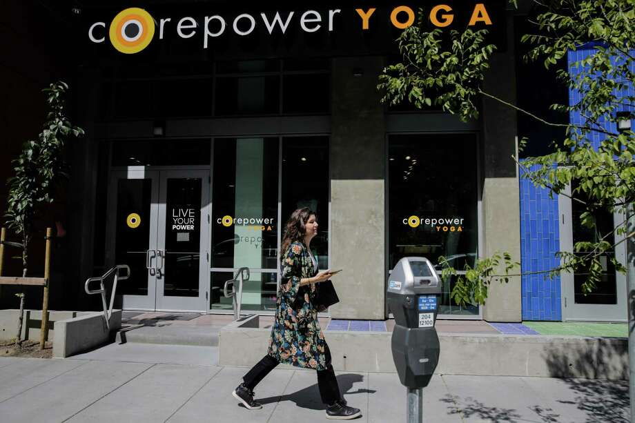 A woman walks past Corepower yoga, a new yoga studio on Fourth Street in Mission Bay in San Francisco, Calif., on Wednesday, July 12, 2017. Photo: Gabrielle Lurie / The Chronicle / ONLINE_YES