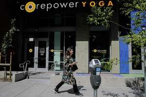 A woman walks past Corepower yoga, a new yoga studio on Fourth Street in Mission Bay in San Francisco, Calif., on Wednesday, July 12, 2017.