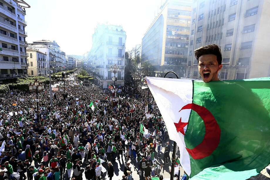 A man shouts as he holds the national flag during a protest in Algiers. Tens of thousands of people gathered in Algeria's capital and other cities amid heavy security for what could be decisive protests against longtime leader Abdelaziz Bouteflika. Photo: Toufik Doudou / Associated Press