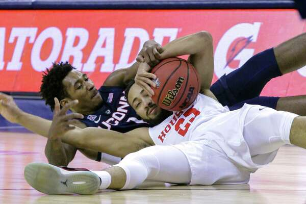 Connecticut guard Christian Vital and Houston's Galen Robinson Jr. scramble for a loose ball during the first half of an NCAA college basketball game at the American Athletic Conference tournament Friday, March 15, 2019, in Memphis, Tenn. (AP Photo/Troy Glasgow)