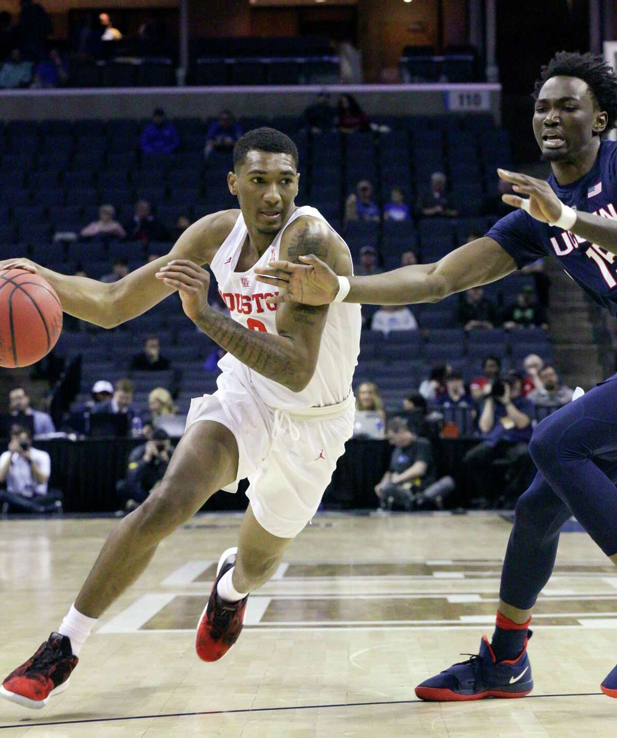 Houston's Armani Brooks, left, drives the ball around Connecticut's Sidney Wilson during the first half of an NCAA college basketball game against Houston at the American Athletic Conference tournament Friday, March 15, 2019, in Memphis, Tenn. (AP Photo/Troy Glasgow)