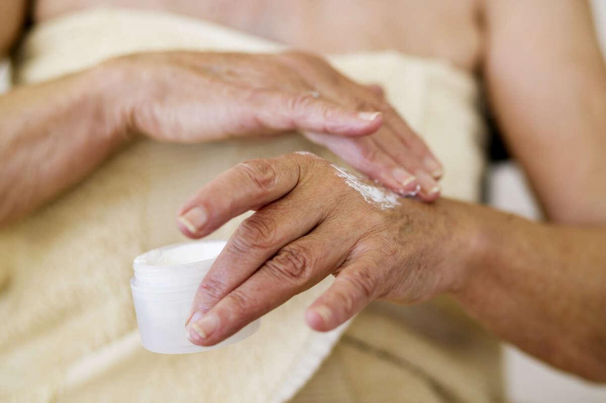 A woman applies moisturizer to her hand.
